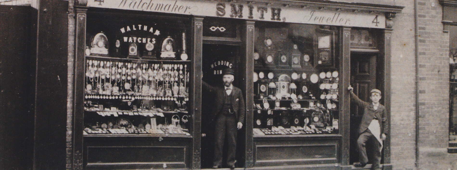 A black and white photo of Angelo Smith standing at the shop door