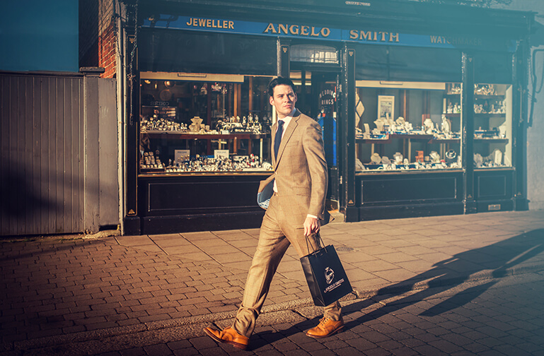 A customer walks past the shop holding an Angelo Smith bag